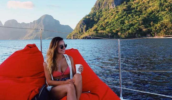 Tourist enjoying the relaxing waters of Palawan while on Catamaran Yacht