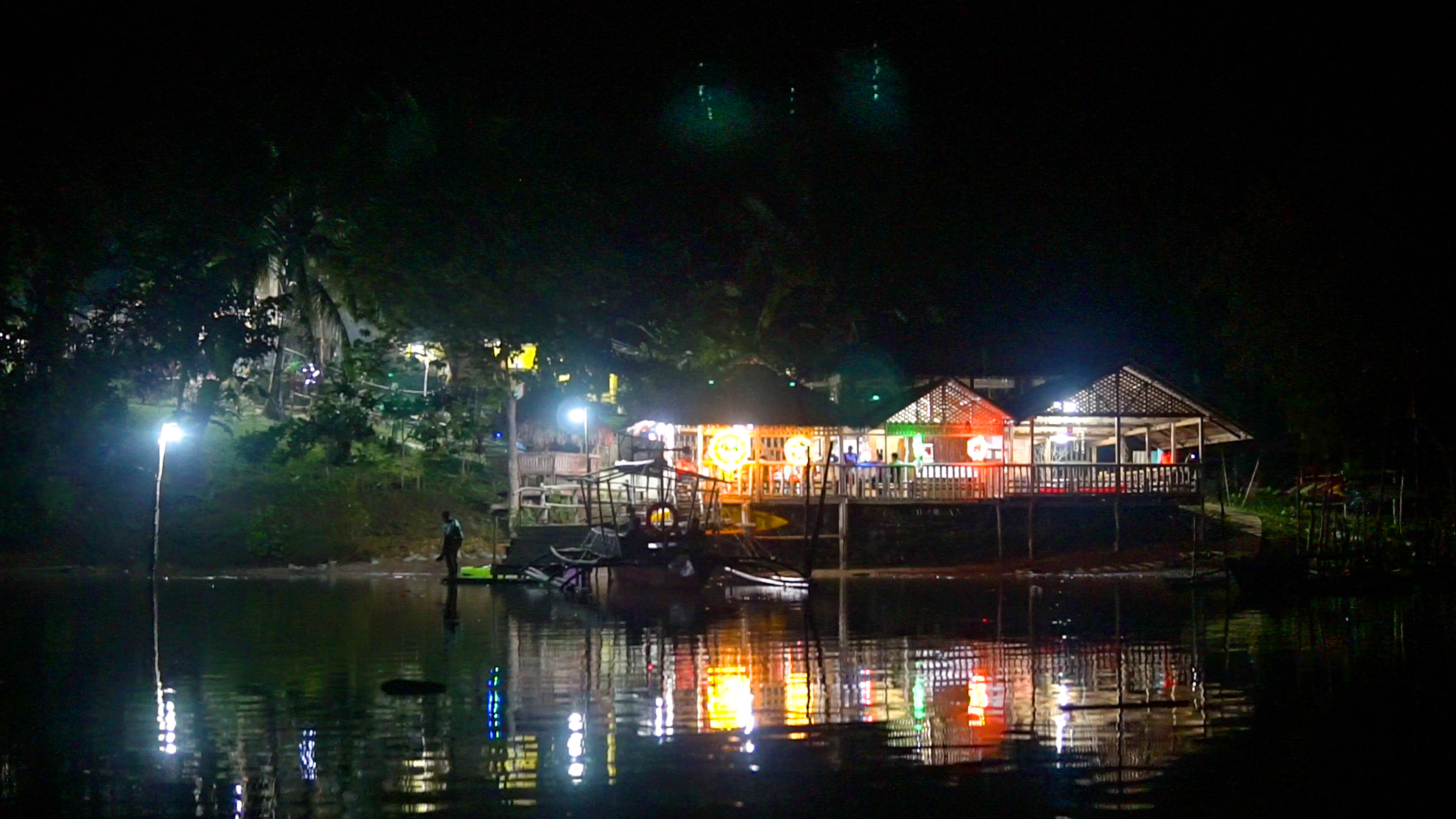 A boat with colorful lights floating on a river in Bohol