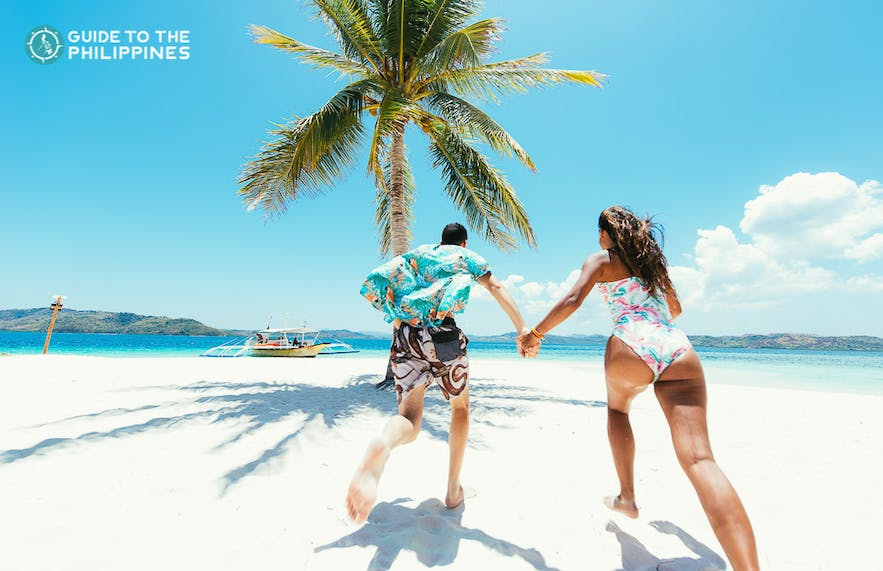 Couple at a white sand beach in Coron, Palawan, Philippines