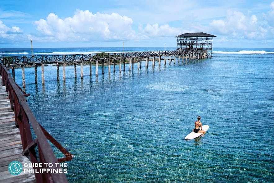 Girl surfing at Cloud 9, Siargao Island, Philippines