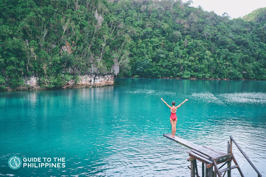 A tourist enjoying the blue tropical lagoon view in Sugba while sitting on its famous wooden springboard.
