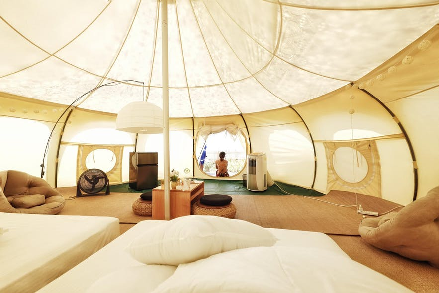 Comfortable and spacious glamping tent surrounded by palm trees at Nacpan Beach in El Nido, Palawan