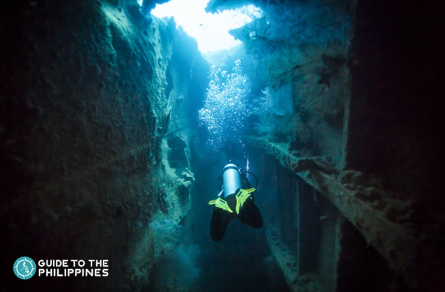 Scuba diver exploring World War II shipwreck in Coron, Palawan