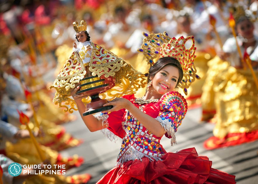 Street performer holding a Sto. Niño during Sinulog festival
