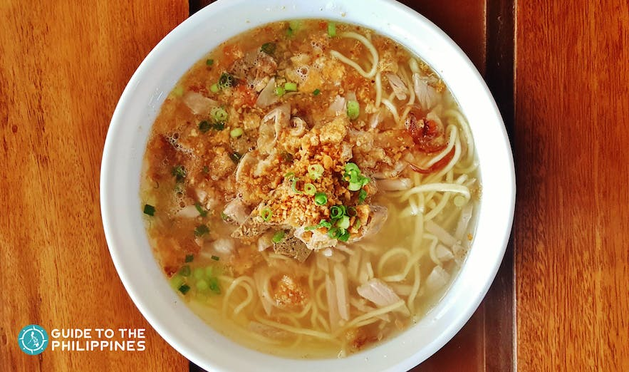 La Paz Batchoy, a clear noodle soup with pork cracklings, beef, chicken stock, and round noodles