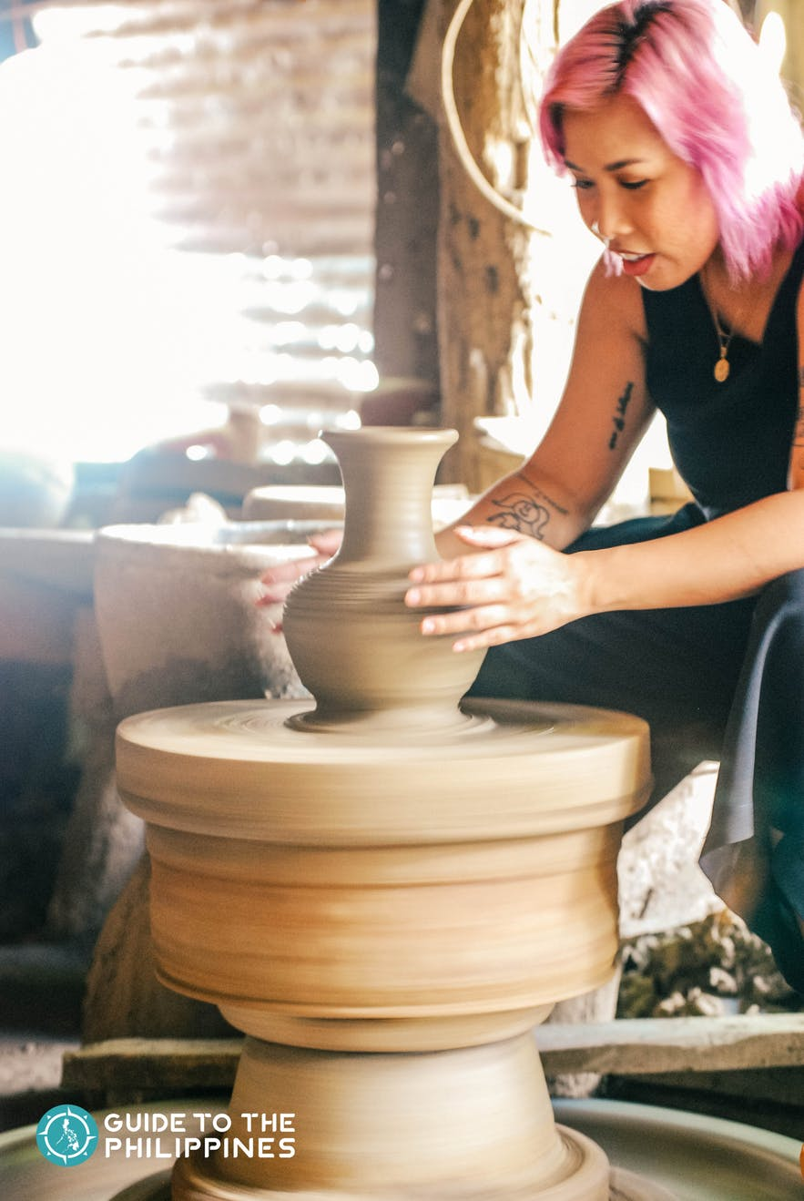 Female traveler learning the basics of pottery making at RG Jar Factory in Vigan