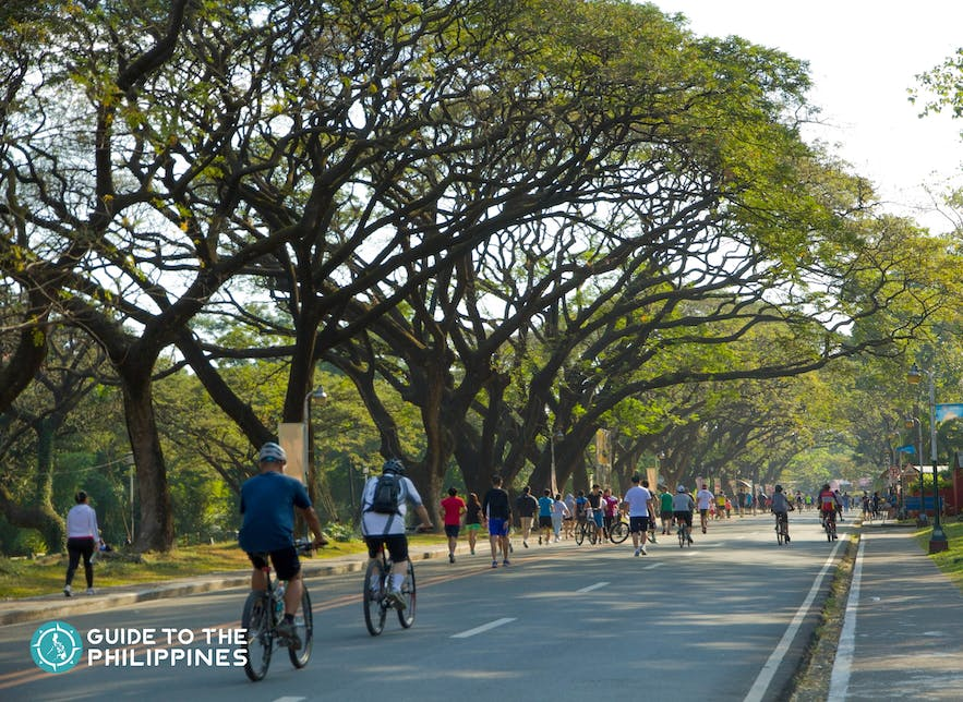 People cycling in the Academic Oval of UP Diliman