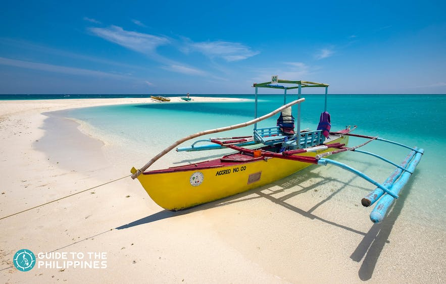 Boat docked on the shores of White Island in Camiguin