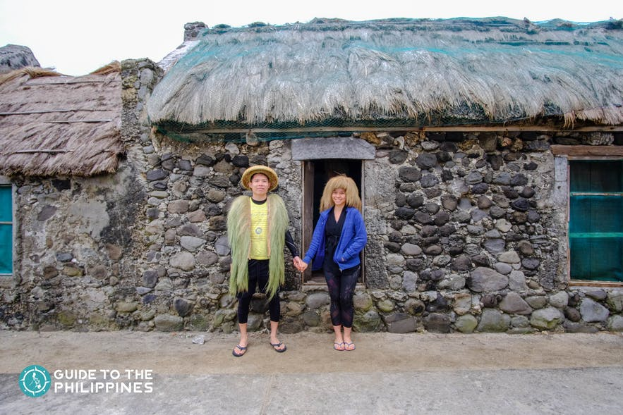 Happy couple travelers wearing native attire in front of a stone house
