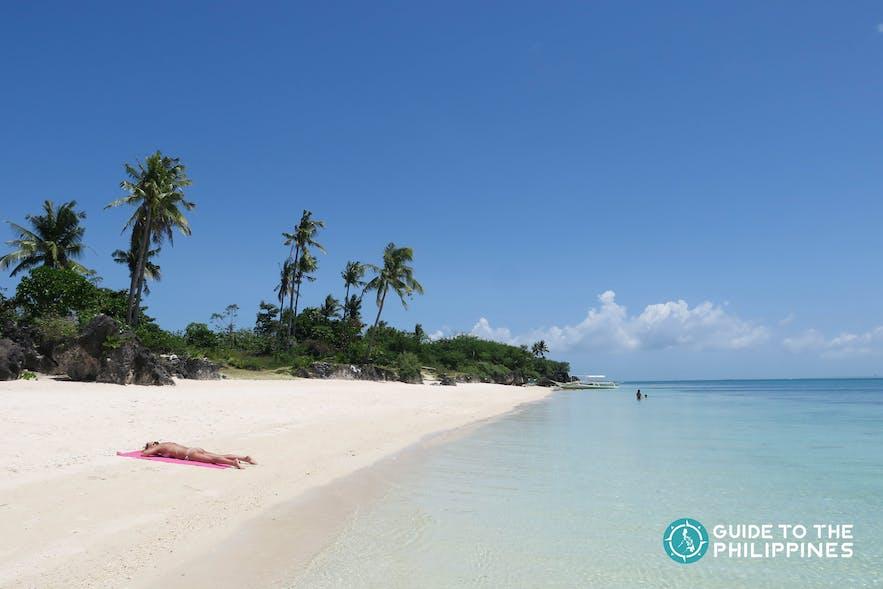 girl lying on the white sands of Paradise Beach