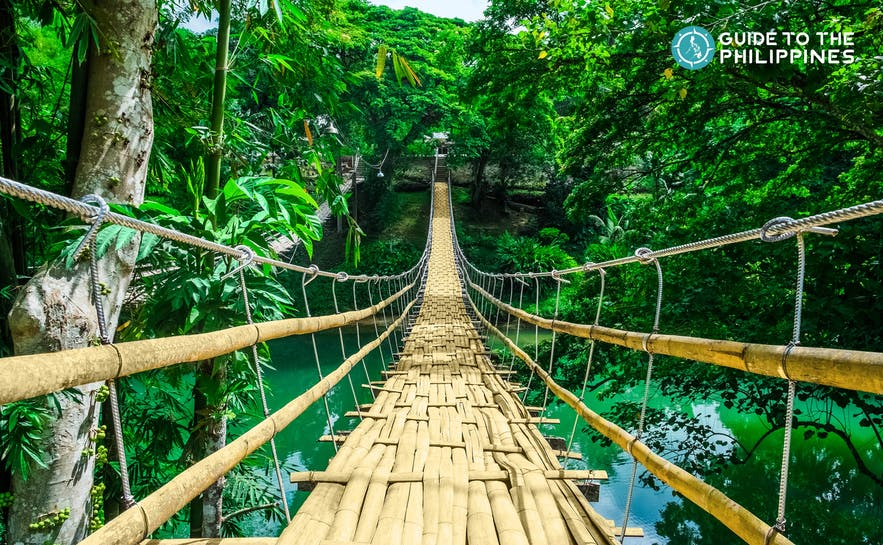Tigbao Hanging Bridge is made of woven bamboo straps and stretches over a gently flowing river