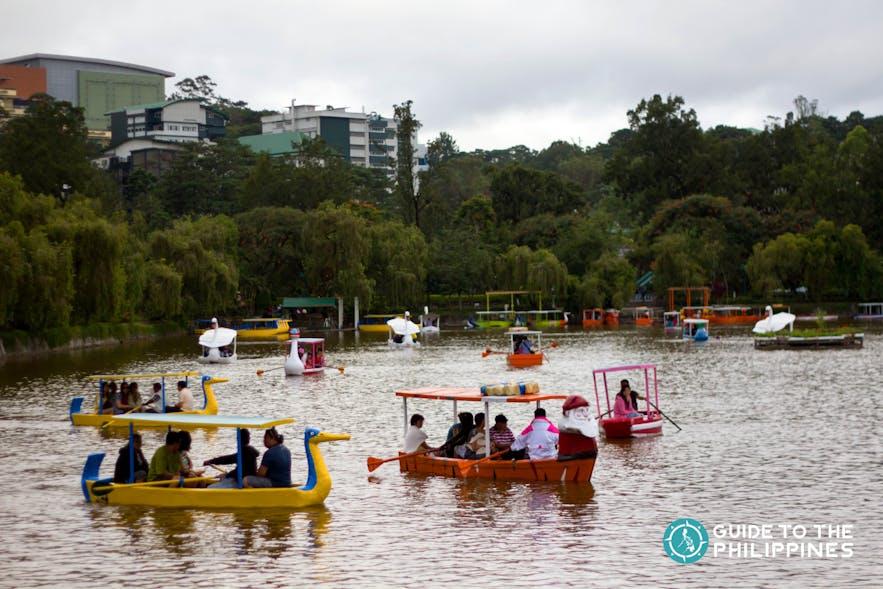 Travelers enjoy boating at Burnham Park in Baguio City, Philippines