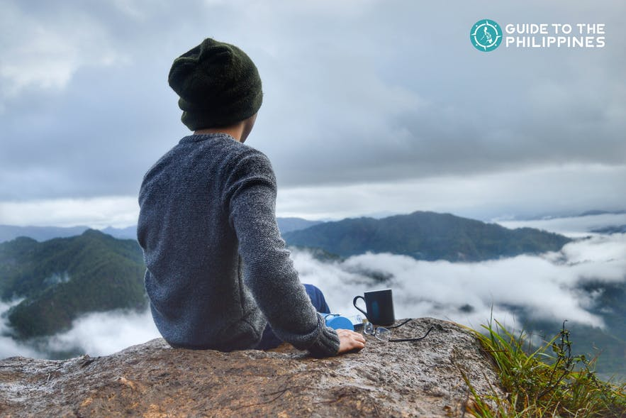 Traveler with a mug of coffee overlooking the mountain peak in Sagada