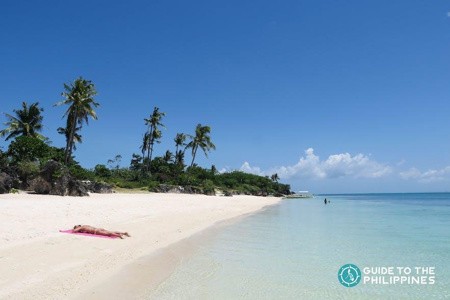 Traveler basking under the sun at Paradise Beach in Bantayan Island of Cebu
