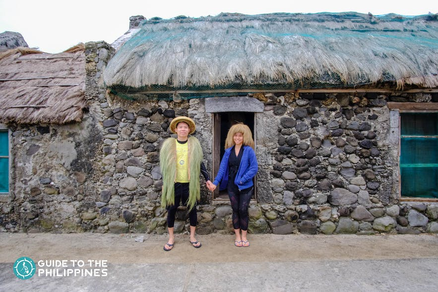 Travelers in front of a typical stone house in Savidug, Batanes