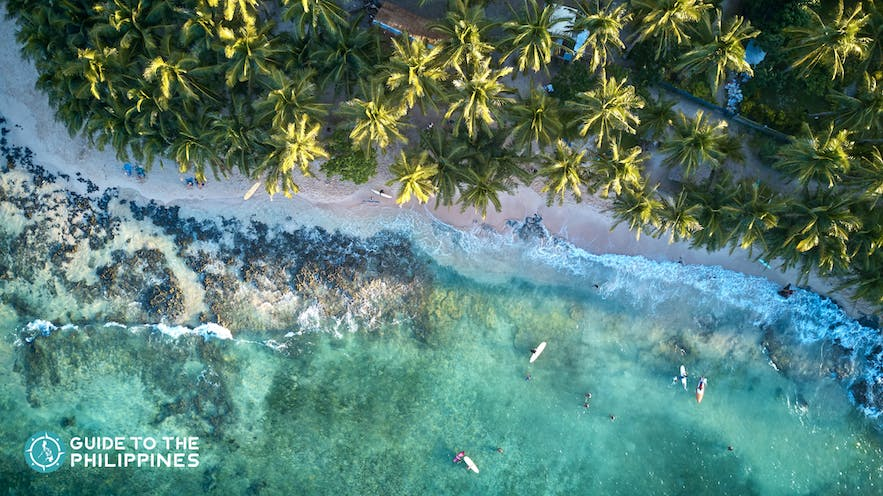 Top view of surfers in Siargao Island's clear waters
