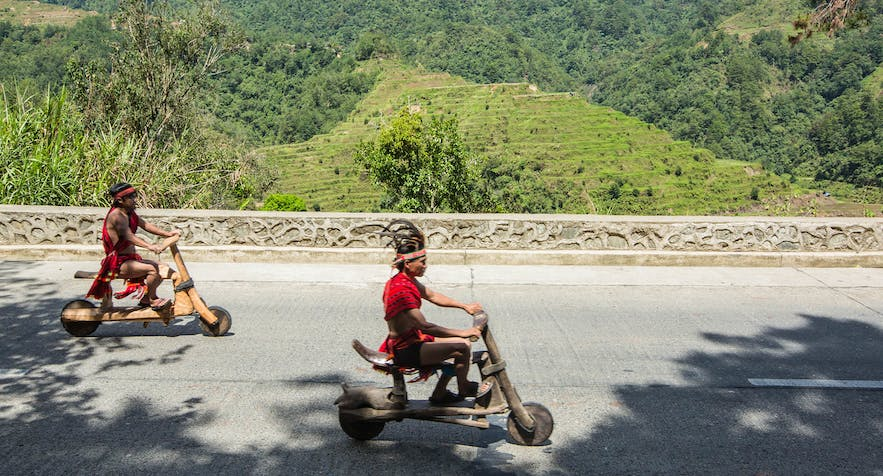 Ifugaos on their wooden scooters in Banaue, Philippines