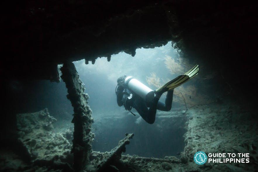Scuba diver exploring World War II shipwreck in Coron, Palawan