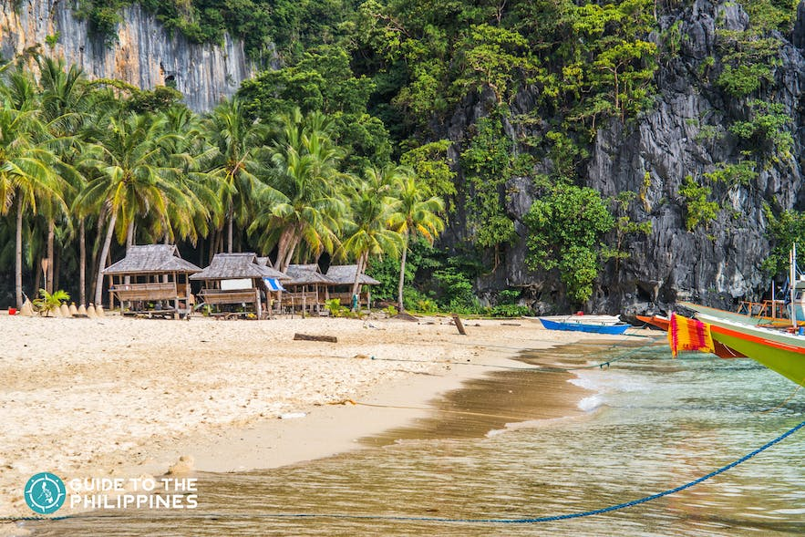 Cottages and boats docked in Seven Commandos Beach in El Nido, Palawan