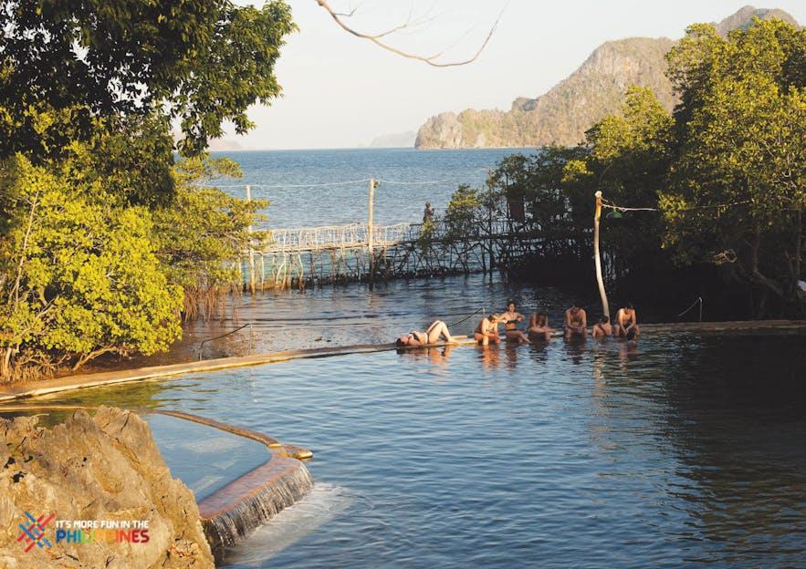 Travelers bathe in Coron's Maquinit Hot Spring