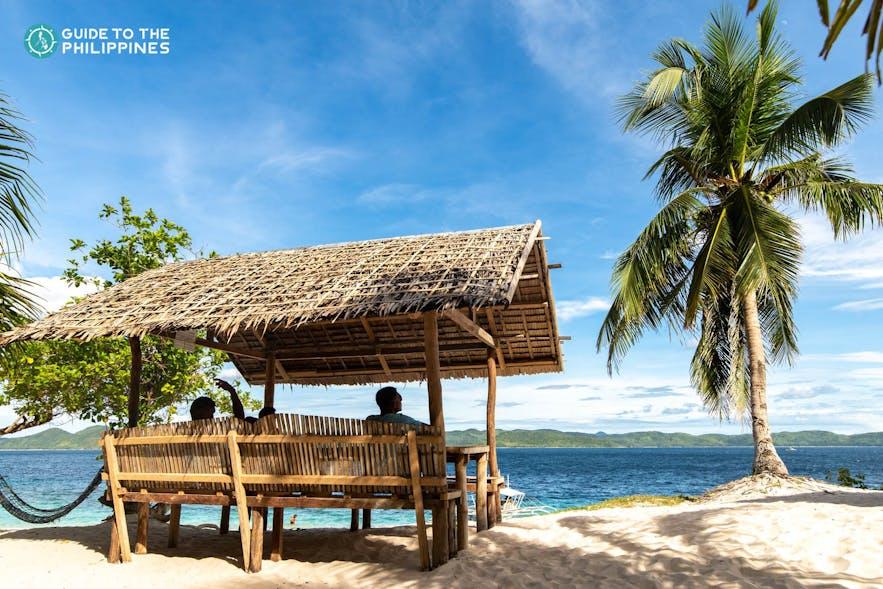 Travelers enjoying the beach view of Coron's Black Island in Busuanga