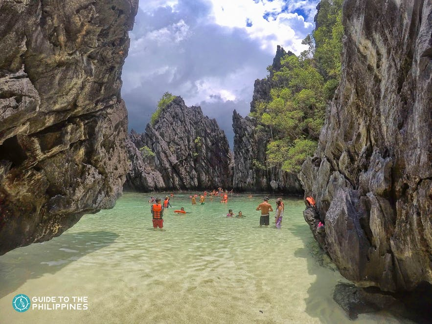 Travelers swimming at the Secret Beach in El Nido, Palawan