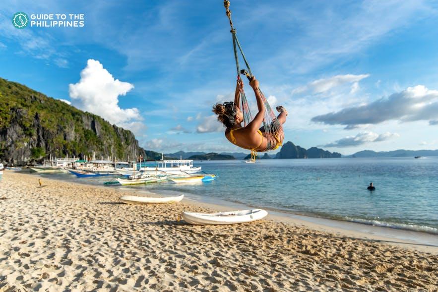 Traveler swinging and enjoying the beach in Palawan
