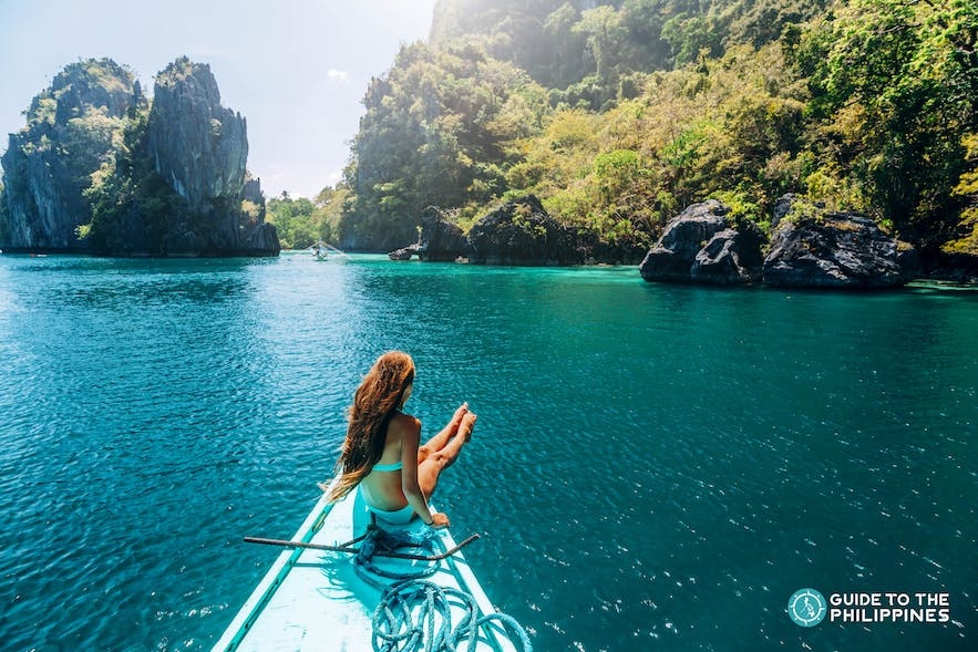 Traveler on the tip of a boat in Palawan