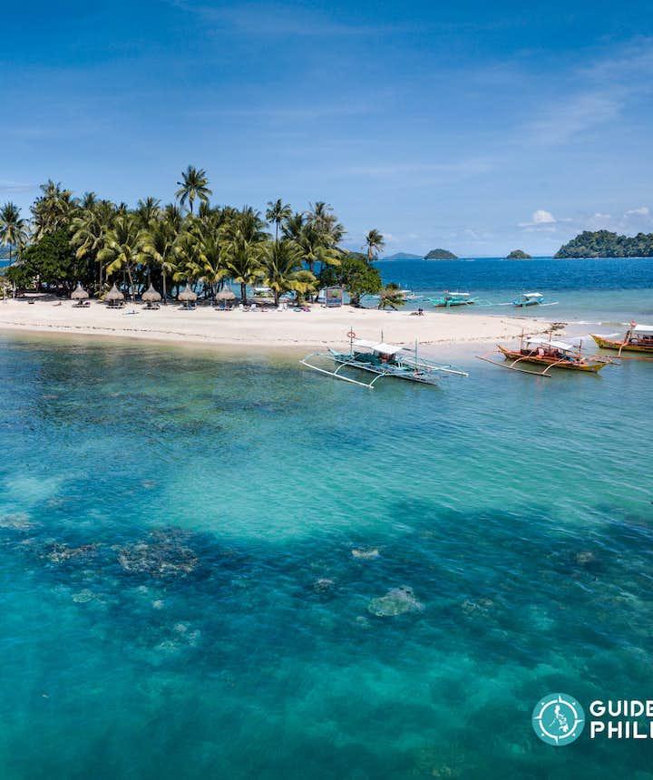 Beach huts and boats at Inaladelan Island in Palawan