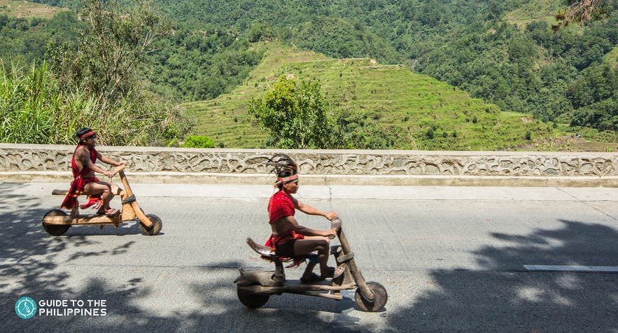 Locals passing by the Banaue Rice Terraces on their wooden scooters