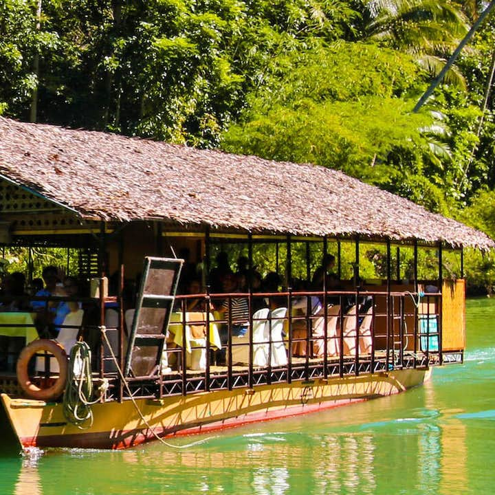 Loboc River Cruise with many tourists eating inside the boat