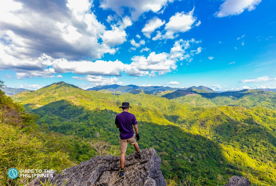Hiker on a rock formation overlooking a lush mountain view