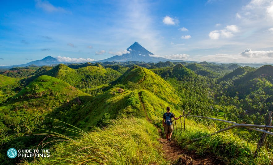 Hiker at Quitinday Hills overlooking Mt. Mayon in Legazpi, Albay, Philippines
