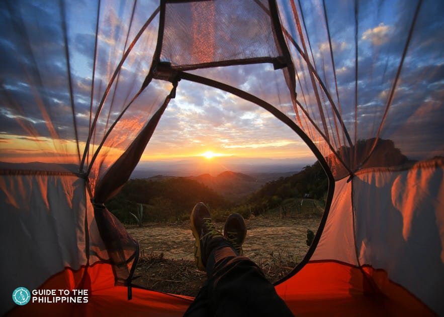 Sunset view from a tent set up for an overnight camping adventure