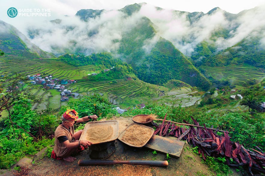 Old woman in traditional tribal clothes overlooking Banaue Rice Terraces