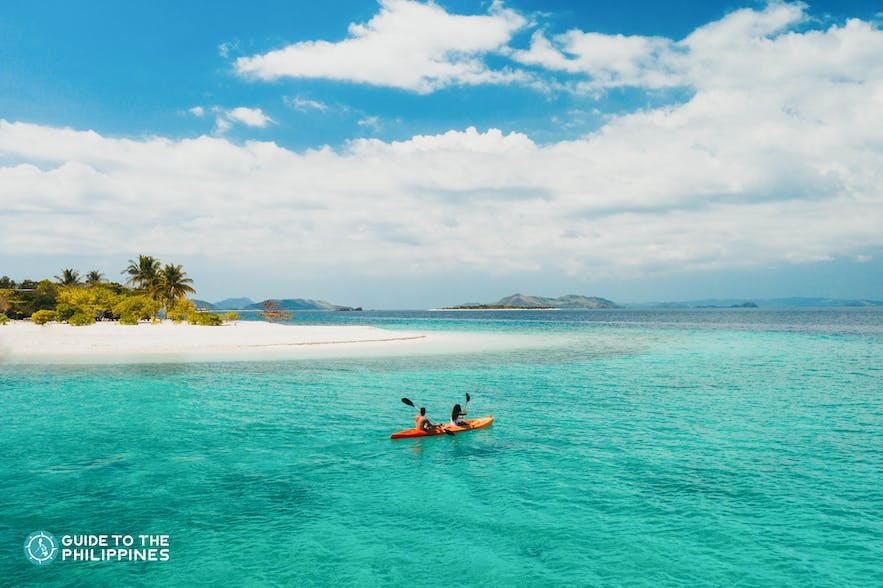 Couple kayaking beside an island in the Philippines