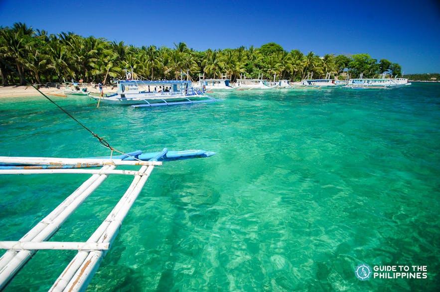 Boat approaching Hilutungan Island's shore