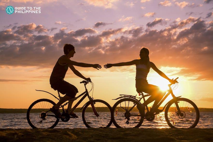 Couple biking at sunset in Manila