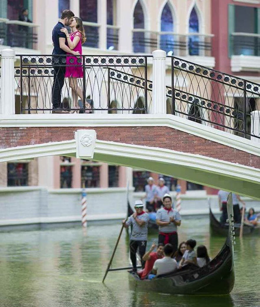 Couple kissing at the bridge over the Venice Grand Canal Mall