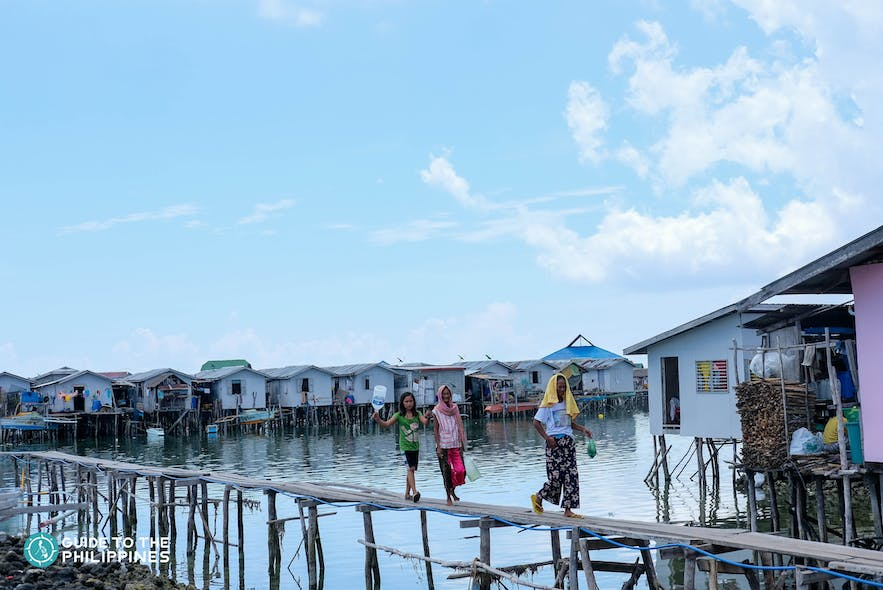 Locals walking along stilt houses in Tawi-Tawi, Philippines