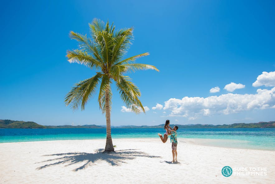 Couple on a tropical beach with blue waters in Coron, Philippines