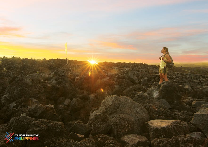 A girl hiking Mayon Volcano during sunset