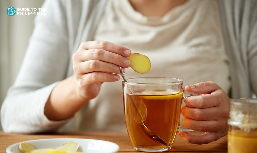 Woman drinking a cup of ginger tea