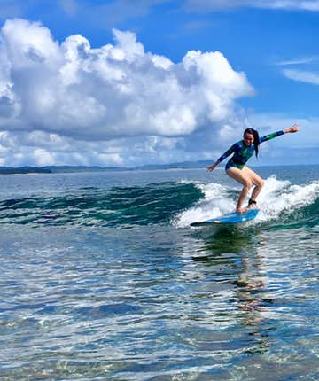 Girl surfing at Siargao surf spot