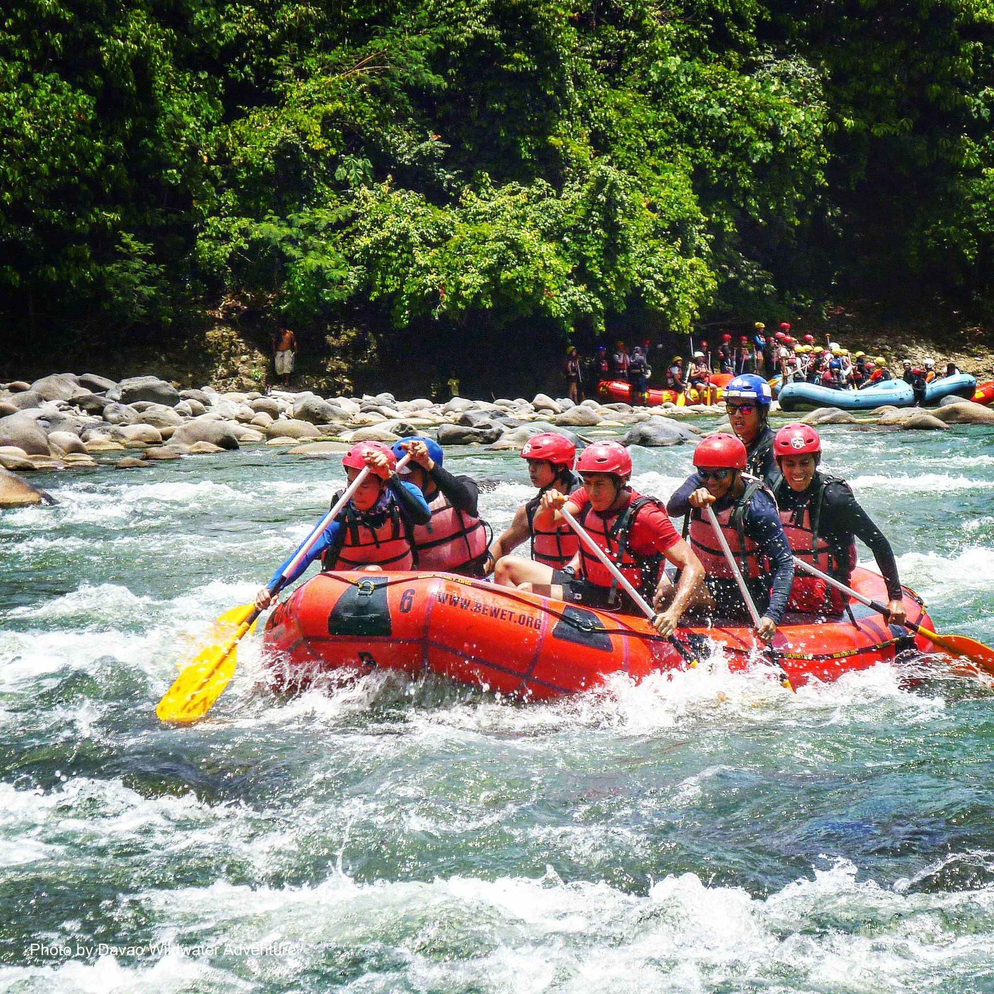 People going to the strong currents during a wildwater rafting experience in Davao