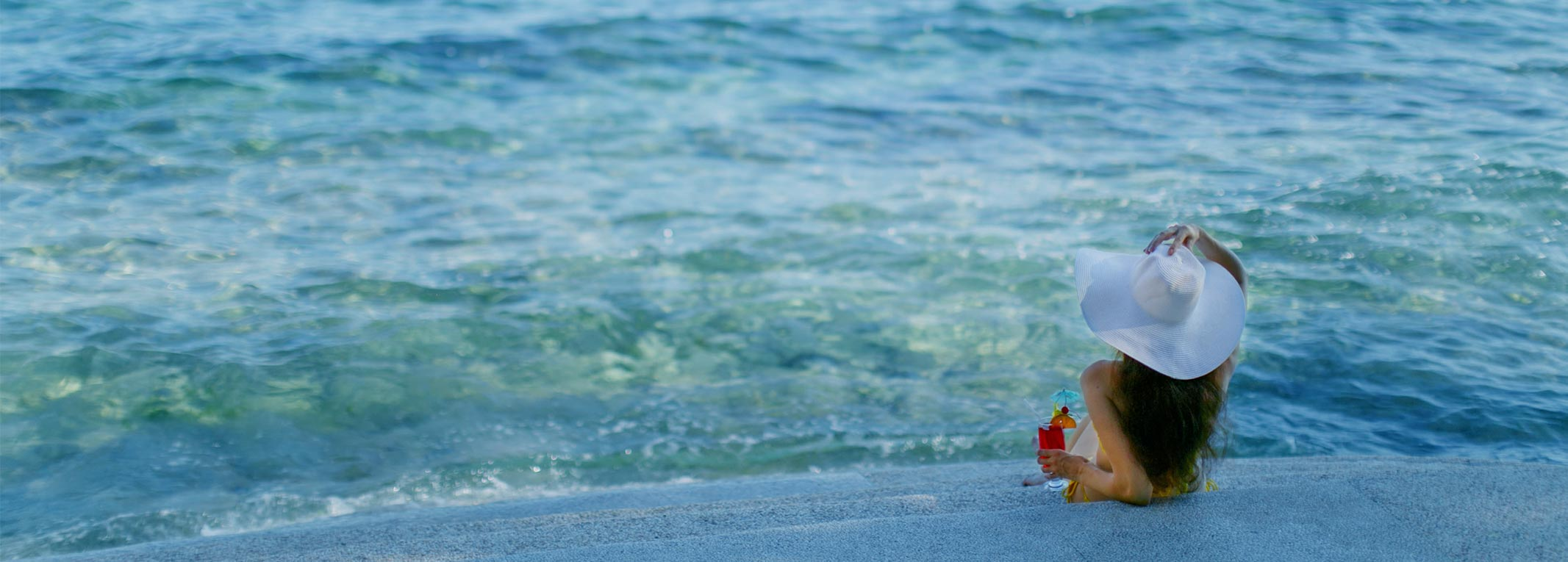 A girl holding a red cocktail while enjoying the view of the beach