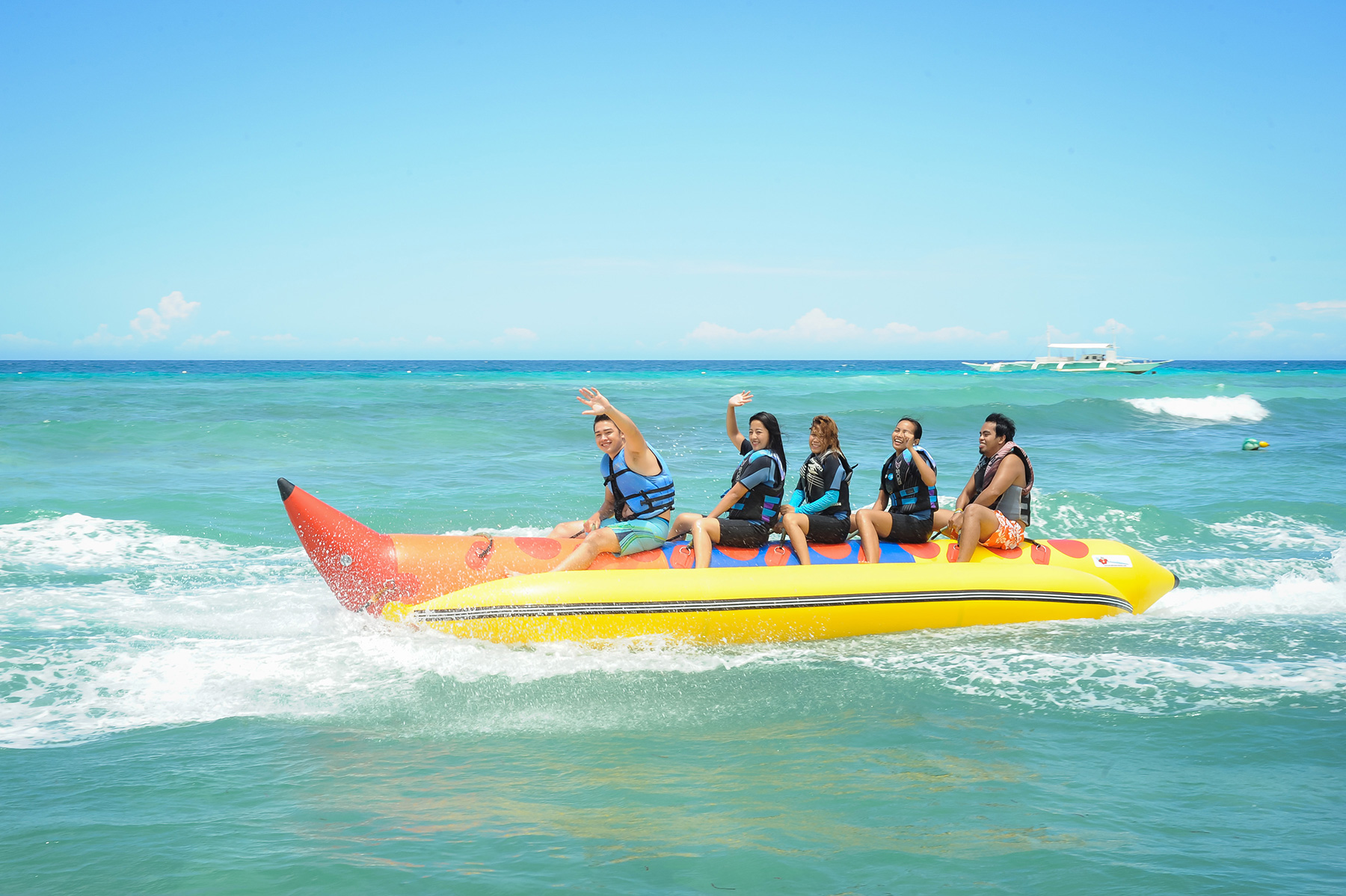 Five travellers enjoying the banana boat ride offered by Bohol Beach Club