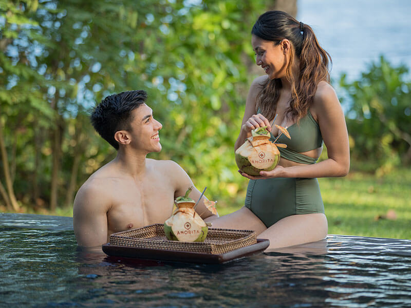 Couple enjoying coconut drink at one of the pools of Amorita Resort