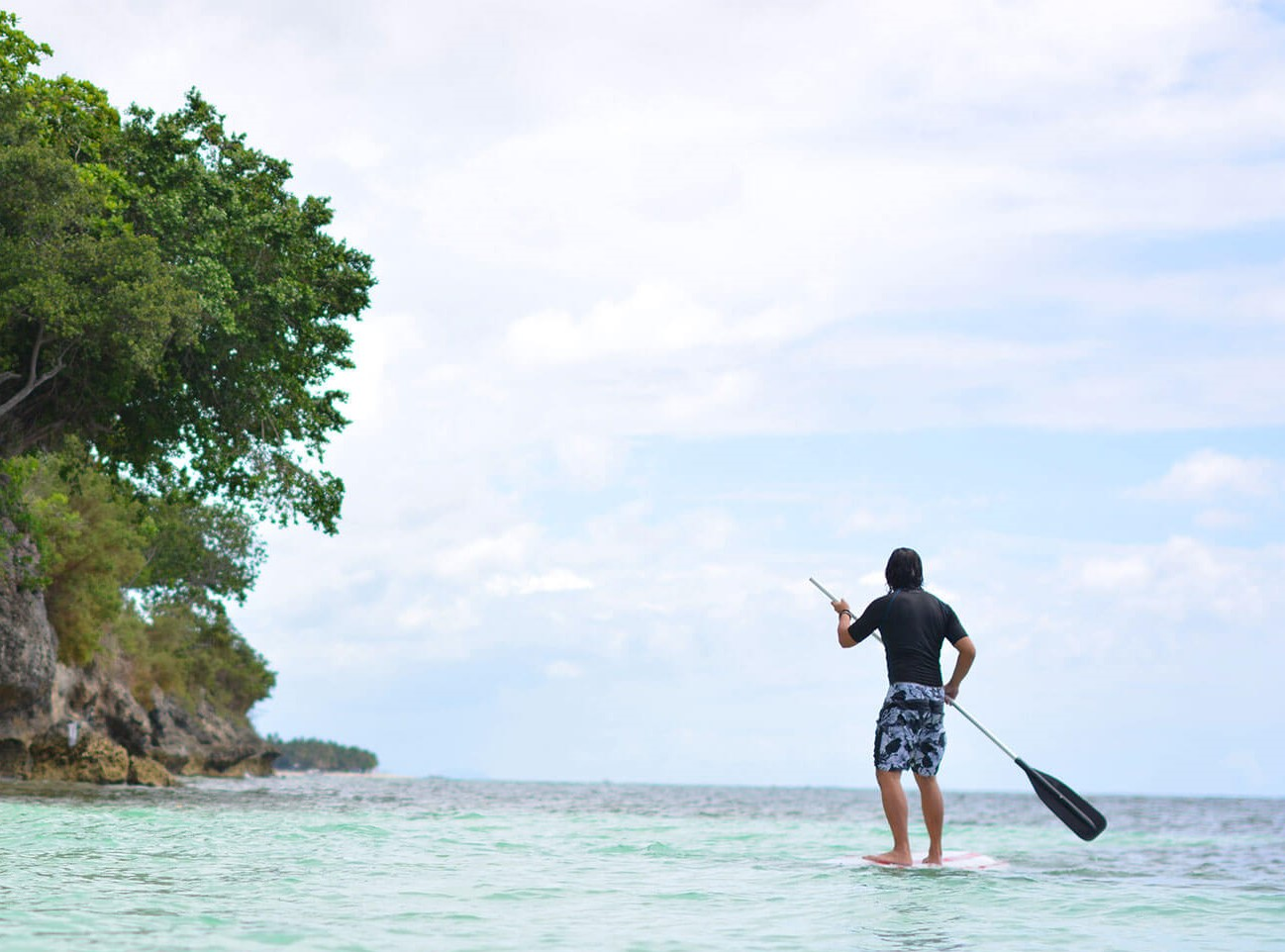 Man enjoying the stand up paddle on a sunny day at Amorita