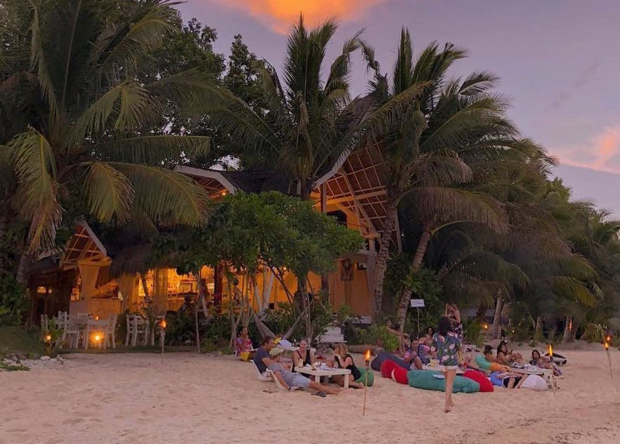 People relaxing on the beach of White Banana Beach Club